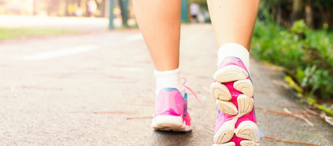 photo-of-woman-wearing-pink-sports-shoes-walking-1556710